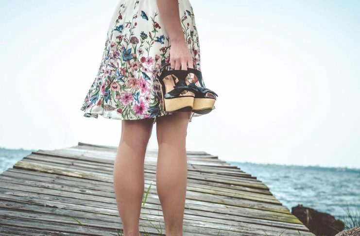 Girl in skirt standing on a pier