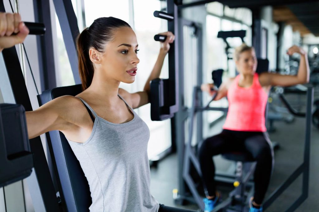 young women exercising on machine in gym