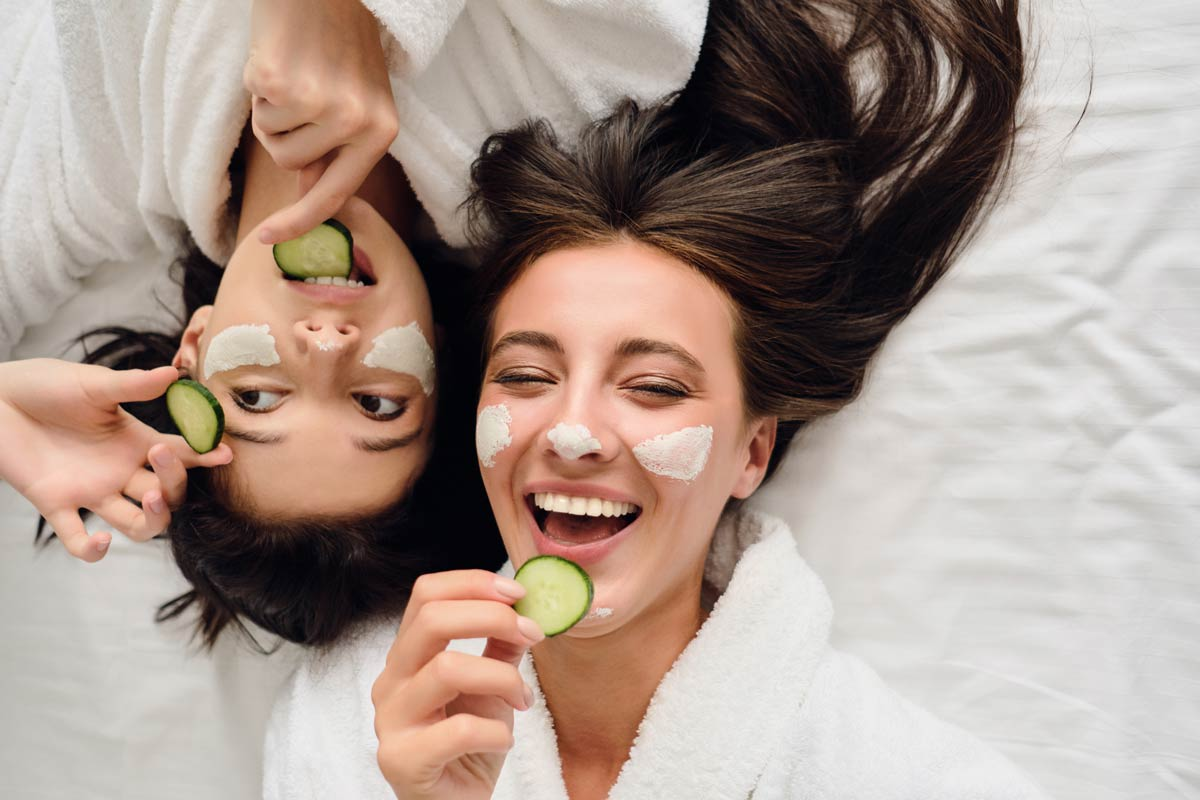 Two young women in bathrobes lying in bed with cosmetic mask on faces happily eating cucumber slices